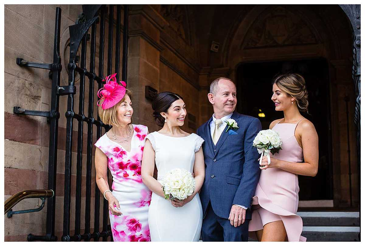 bride with her mum, dad and sister outside with chester town hall laughing and smiling between themselves