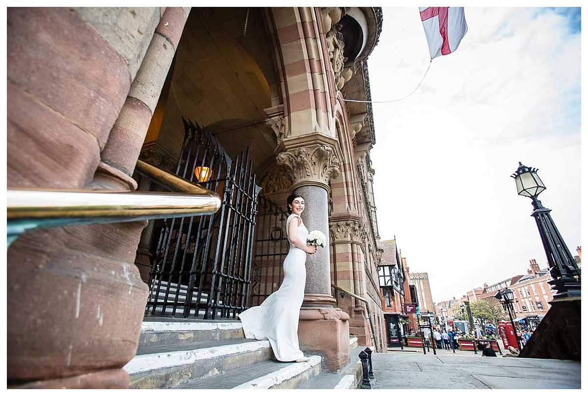 wide shot of the front of the town hall and bride looking incredibly excited