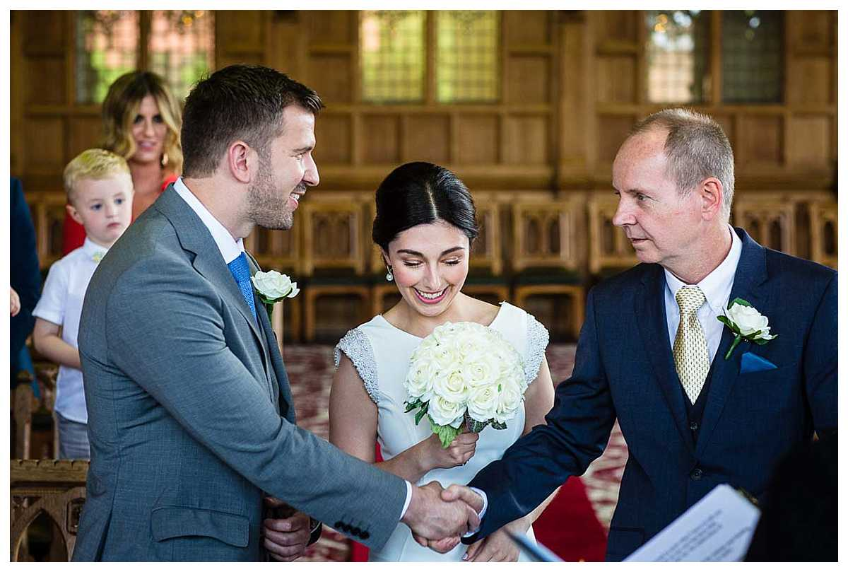 groom and father of the bride shaking hands when they reach the end of the aisle