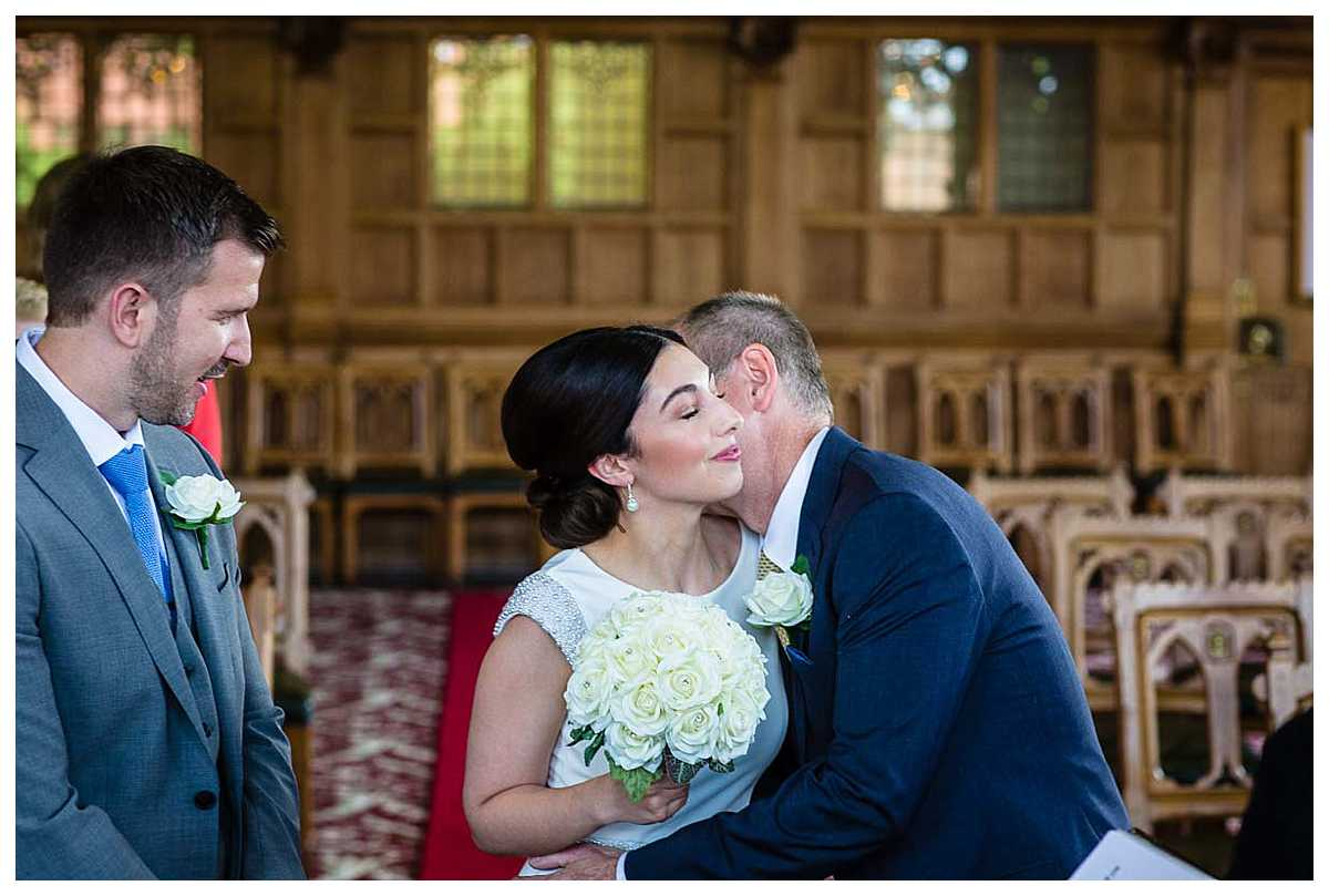 father of the bride giving his daughter a kiss before he gives her away at chester town hall wedding