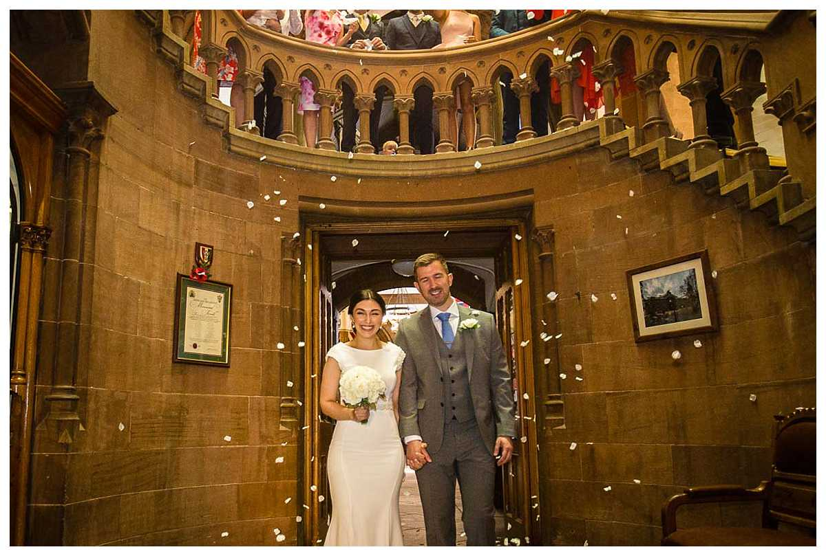 confetti being thrown over the bride and groom high on the staircase in the town hall