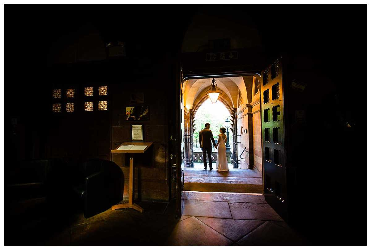 silhouette of the bride and groom walking out of the main door at chester town hall wedding