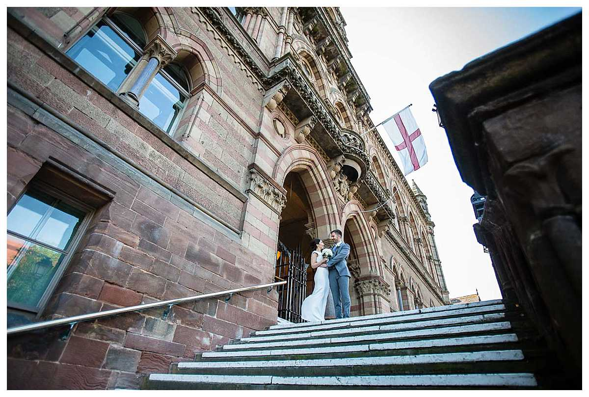 bride and groom at the top of the stairs at the town hall and lots of lovely architectural details