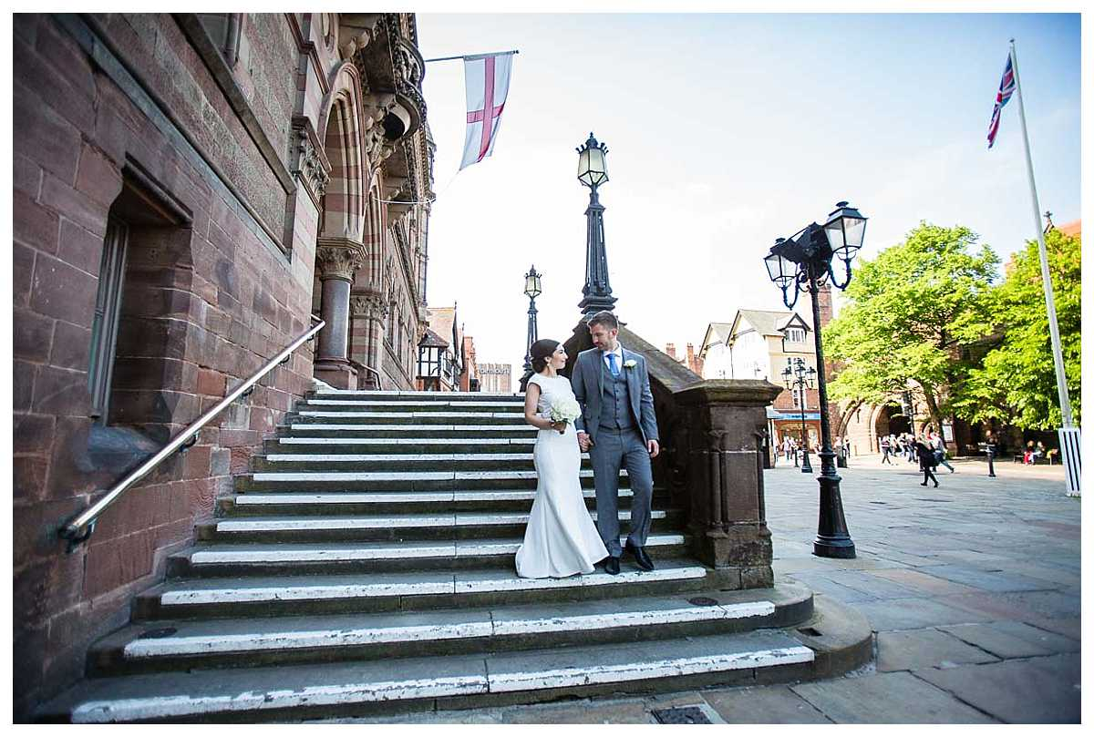 bride and groom looking at one another lovingly as they come down the stairs at the chester town hall