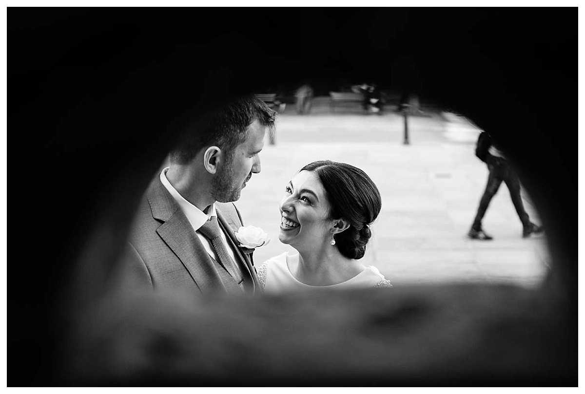 black and white photo of bride and groom looking at each other shooting through the holes in the walls