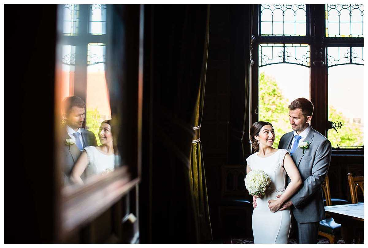 bride and groom nuzzled in together smiling back at each other with reflection looking happy
