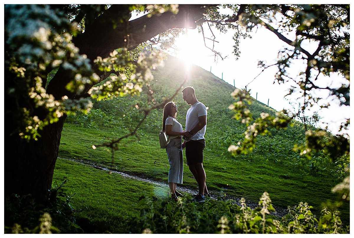 couple having a moment amongst the blossom trees in golden hour pre-wedding shoot llangolllen