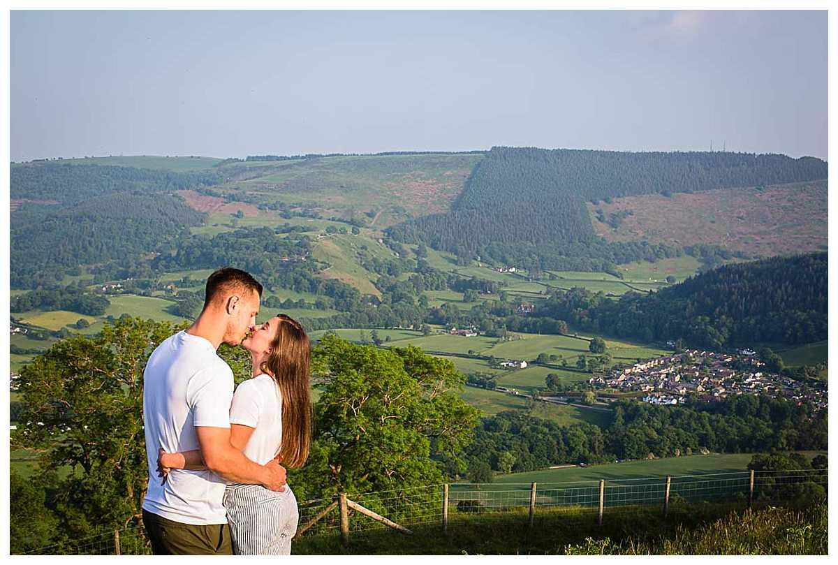 couple kissing with views of llangollen and their wedding venue - tyn dwr, llangollen