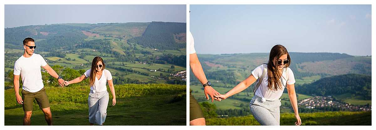 couple holding hands as they walk up castell dinas bran giggling in the golden light