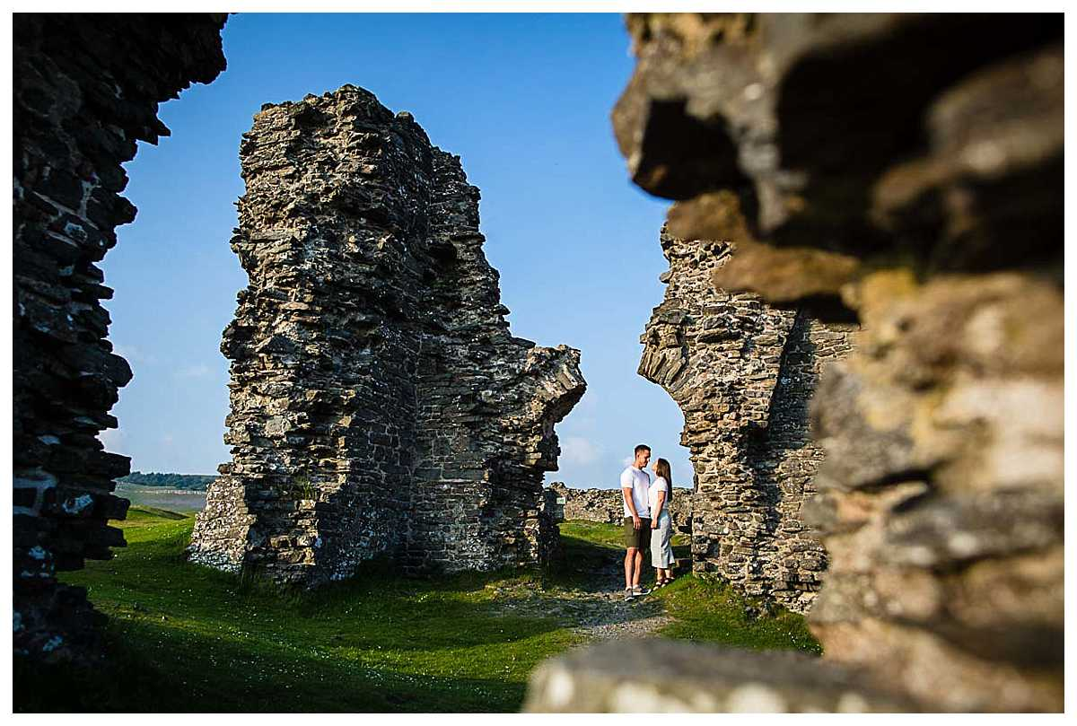 bride and groom to be looking at each other amongst the magnificent ruins at pre-wedding shoot Llangollen