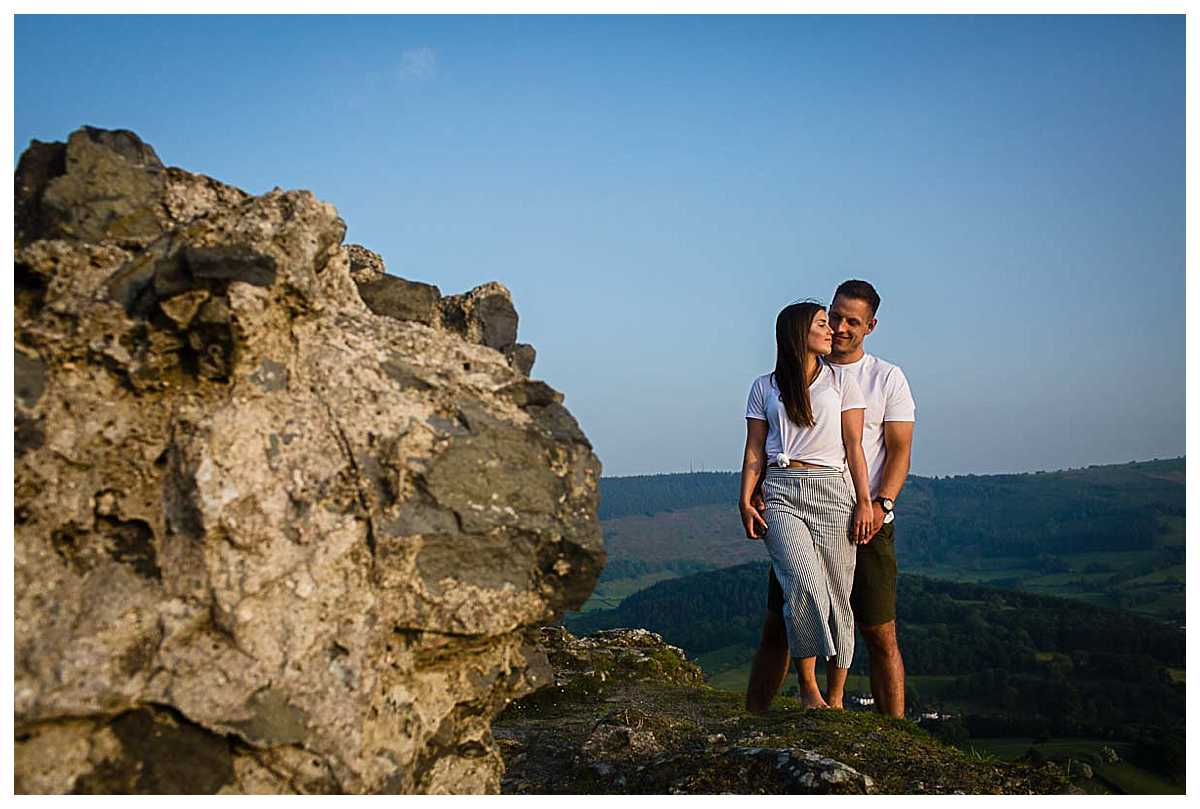 beautiful moment of bride and groom close together with the views of llangollen with blue sky