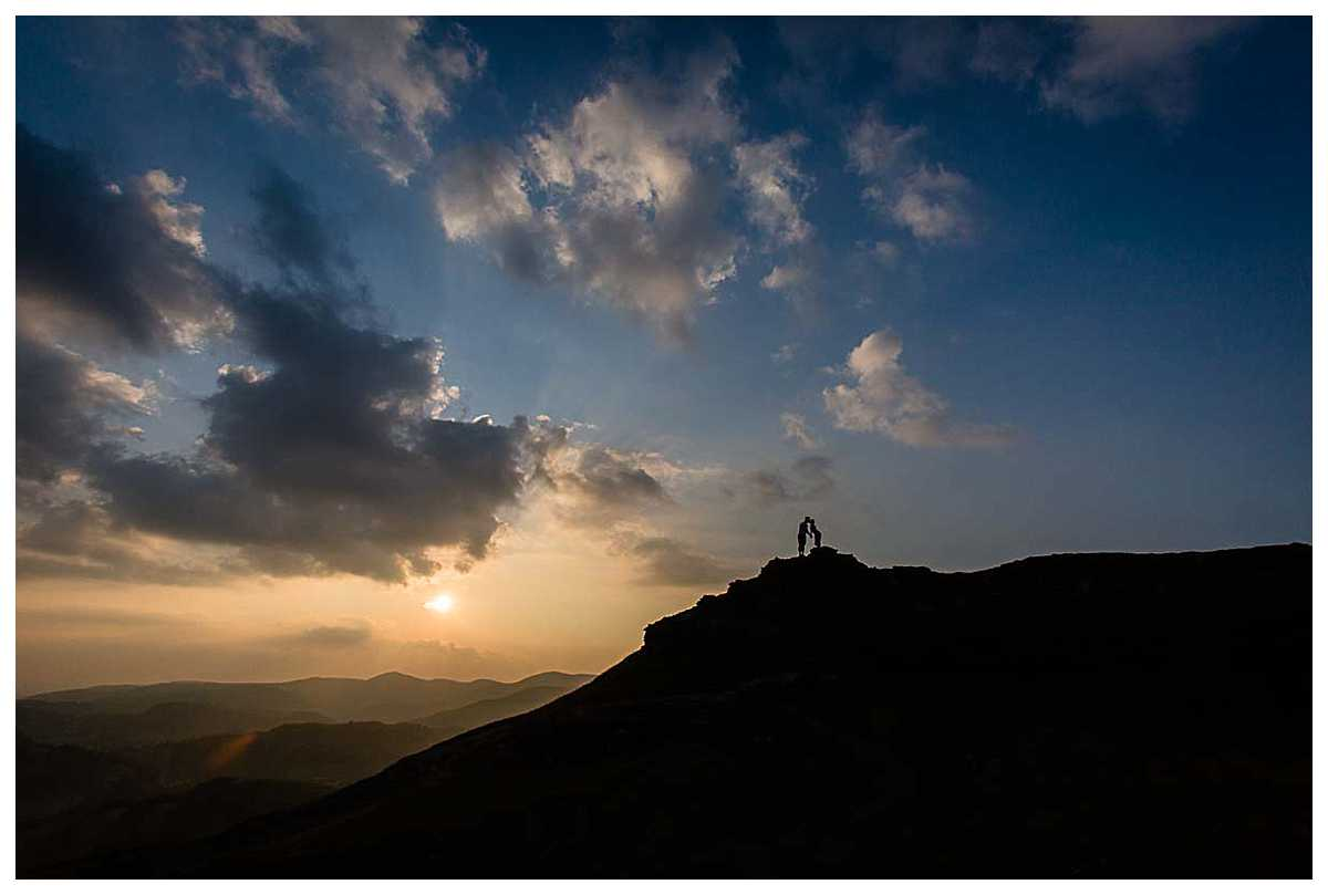 bride and groom on top of the highest point of castell dinas bran - silhouette kissing in the sunshine and amazing sky