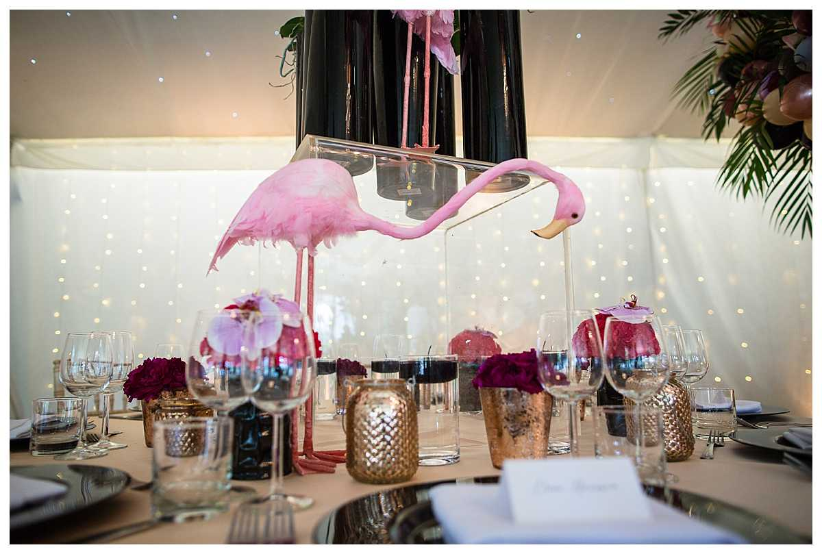 large flamingo statue amongst gold accessories and purple themed flowers