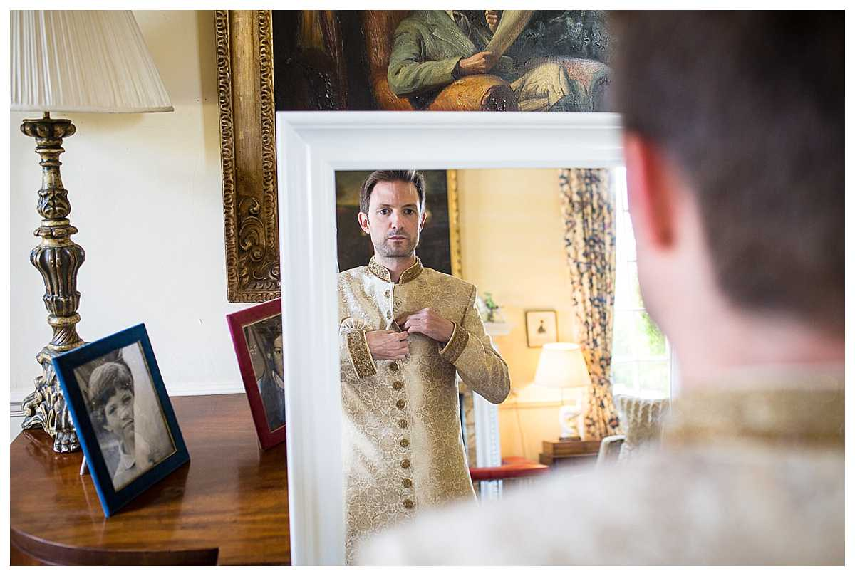 groom watching himself in the mirror as he does up him jacket before he gets married at poundon house, bicester