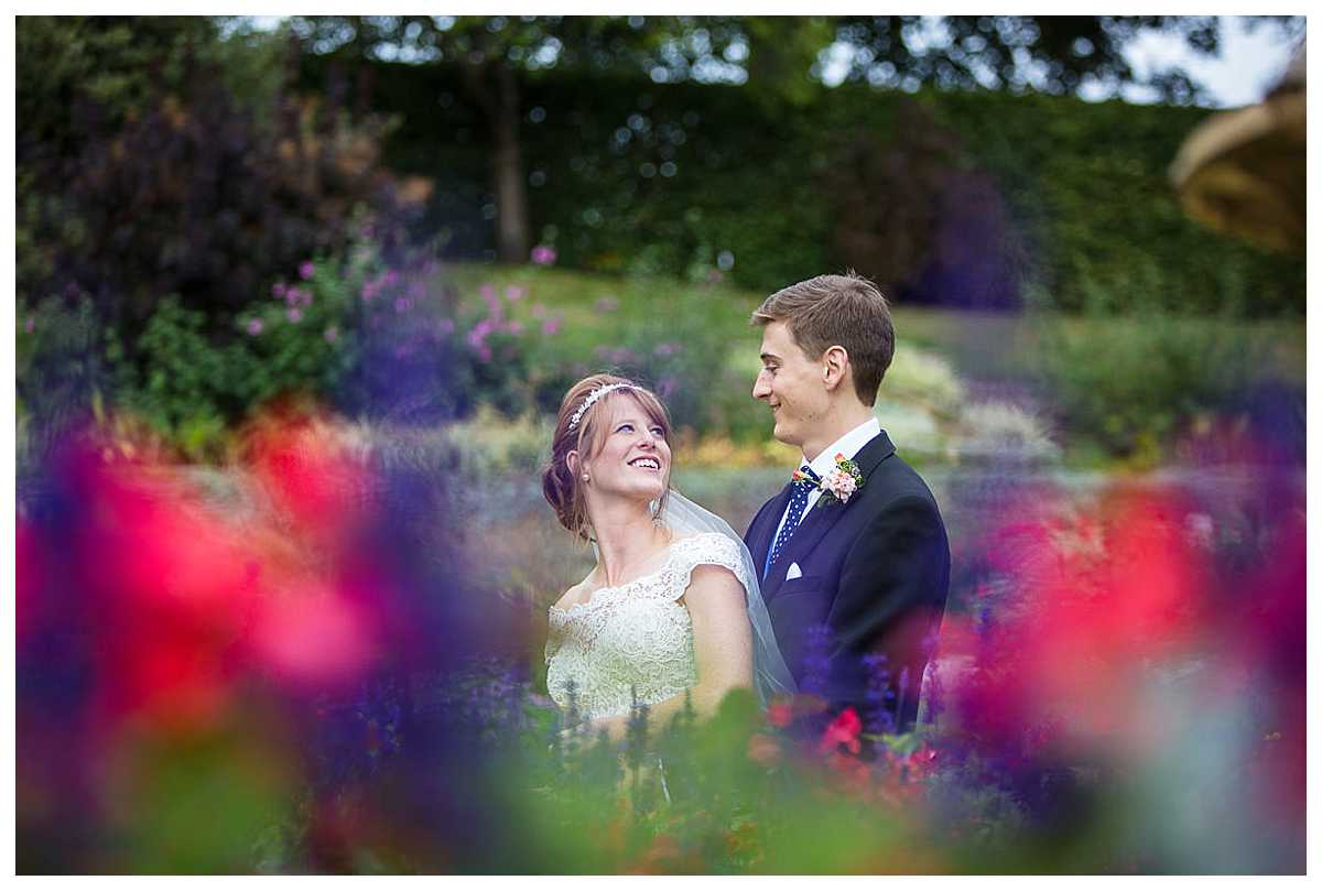 bride and groom standing amongst colour ful bright colourful flowers in The Dingle Shrewsbury.