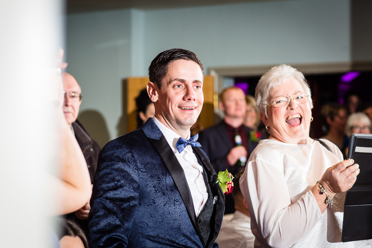 groom looking shocked as his wife announces wedding evening surprise on the band microphone at lake vyrnwy