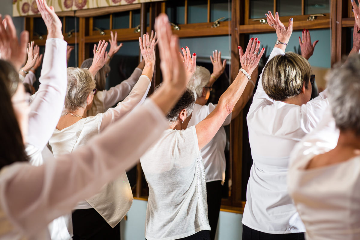 group of dancing women with arms in the air at lake vyrnwy performing to an audience