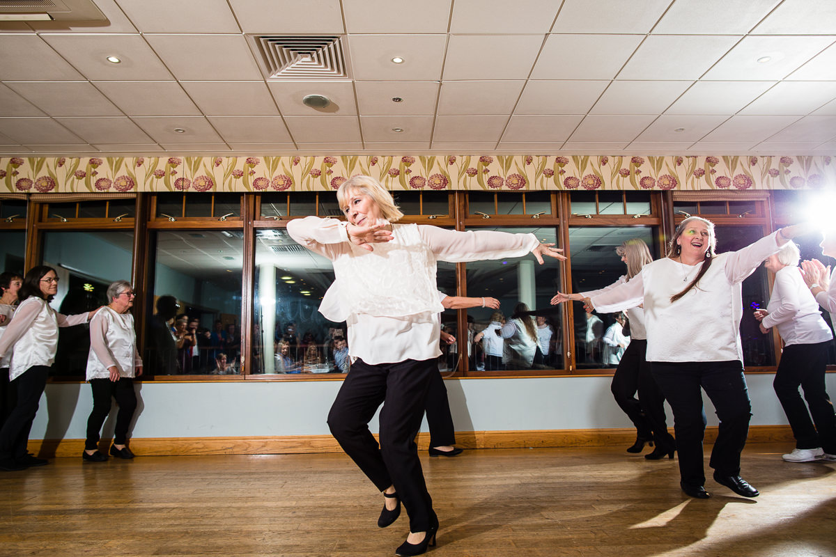 ladies dancing across the hall at lake vyrnwy with arms out part of the routine