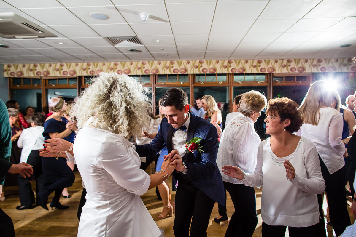 bride and groom amongst their guests dancing away to the live band at lake vyrnwy wedding