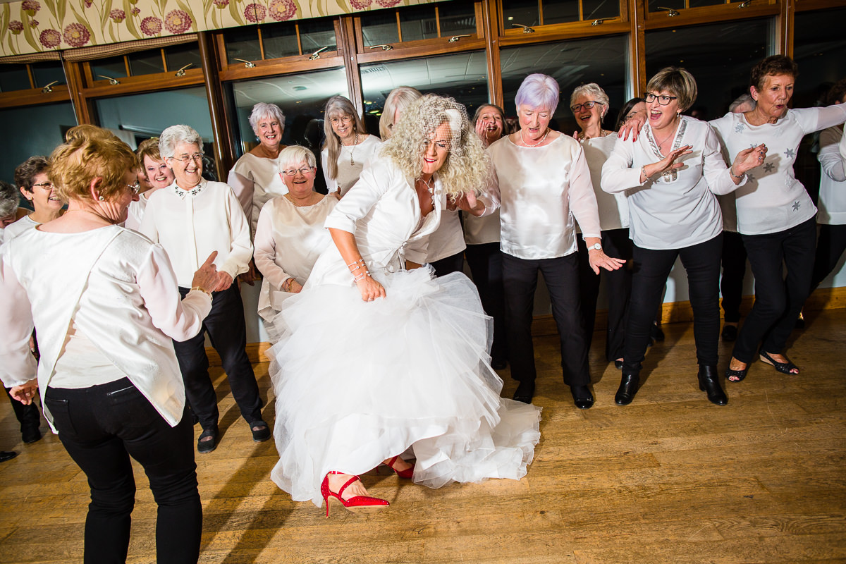 bride dancing with friends showing off her red shoes at lake vyrnwy wedding