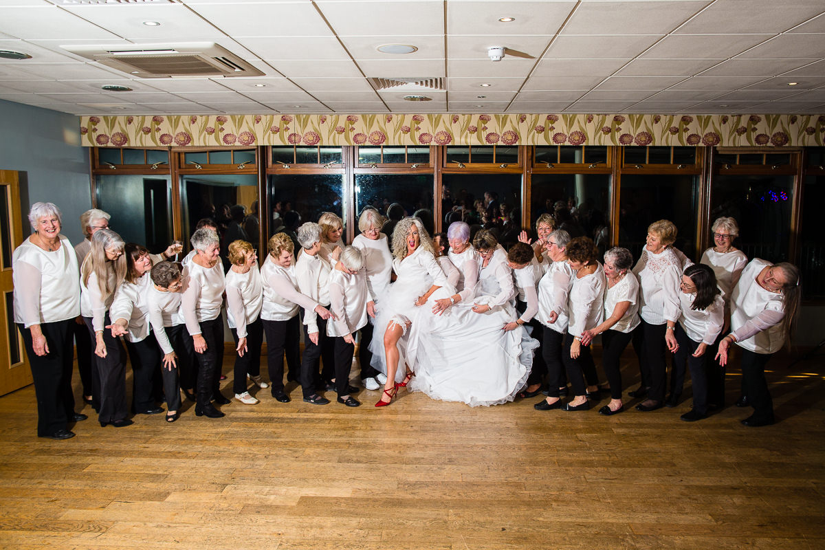 group photo with the bride showing off her red shoes and garter - lake vyrnwy wedding charlotte giddings photography