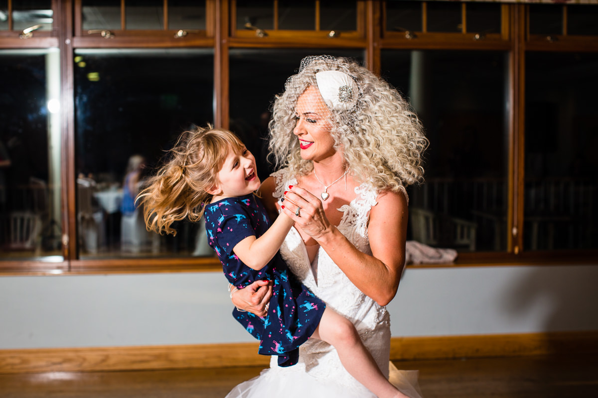 bride dancing away with little girl swishing hair as they dance around at lake vyrnwy evening do -charlotte giddings photography
