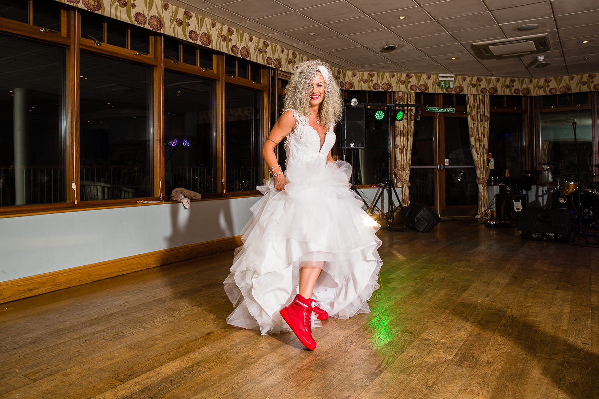 bride posing with red trainers on the dance floor at lake vyrnwy hotel