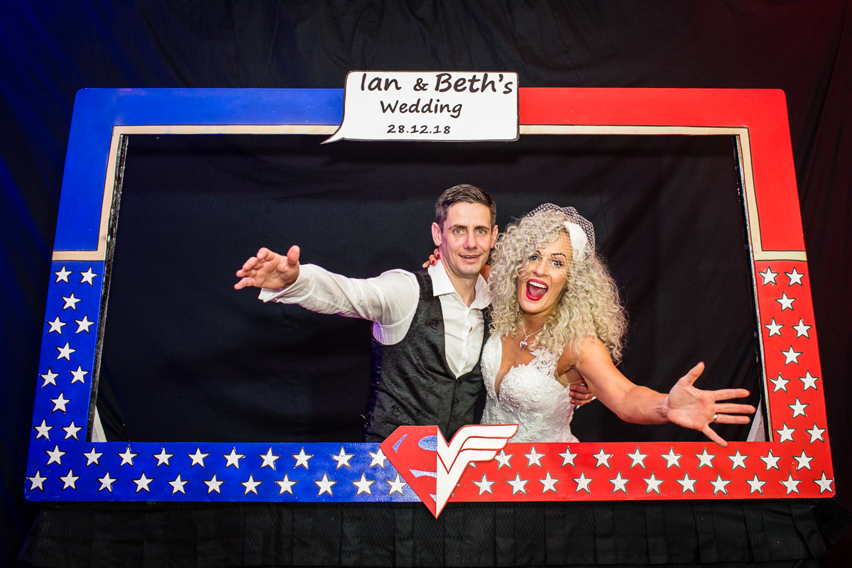 bride and groom posing with their custom made super hero themed photo booth frame at lake vyrnwy hotel wedding