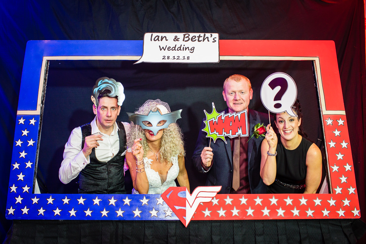 wedding party posing in super hero themed photo booth - with super hero props at lake vyrnwy wedding