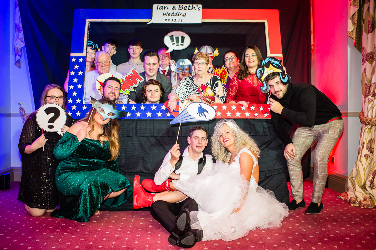 large group of guests posing with super hero themed props and frame at lake vyrnwy hotel wedding