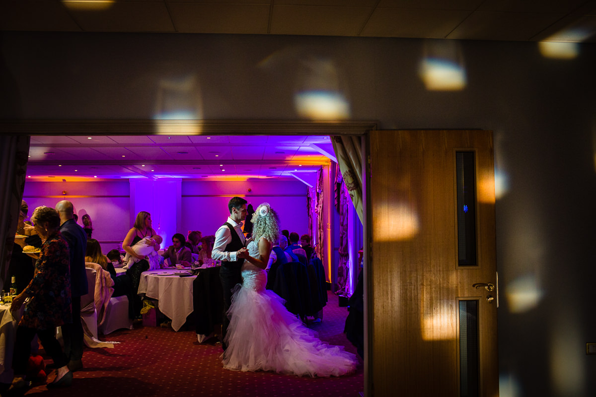 bride and groom slow dancing in other room from the dance floor nice and close - lake vyrnwy hotel wedding