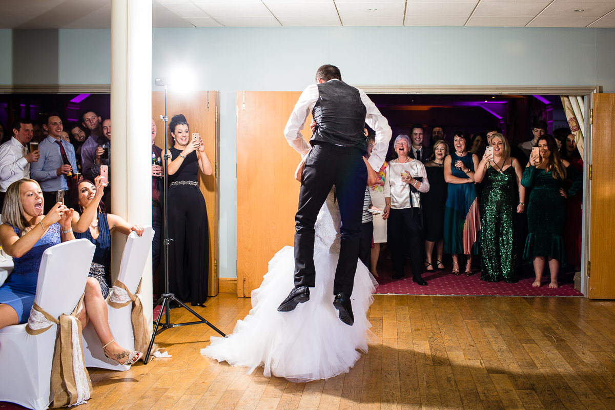 bride lifting the groom for a joke during their first dance at wales wedding venue lake vyrnwy hotel