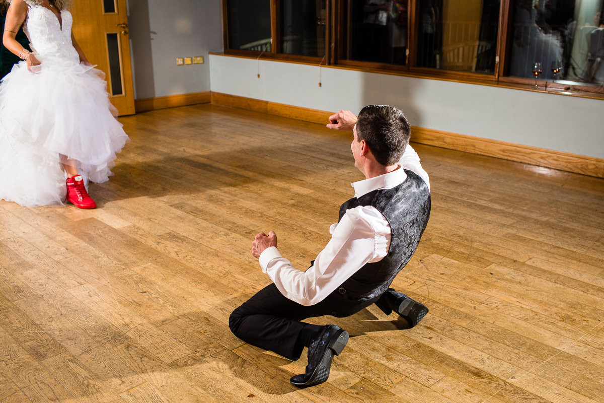 groom down on his knees as bride sexy walks towards him on the dancefloor at wales wedding reception lake vyrnwy