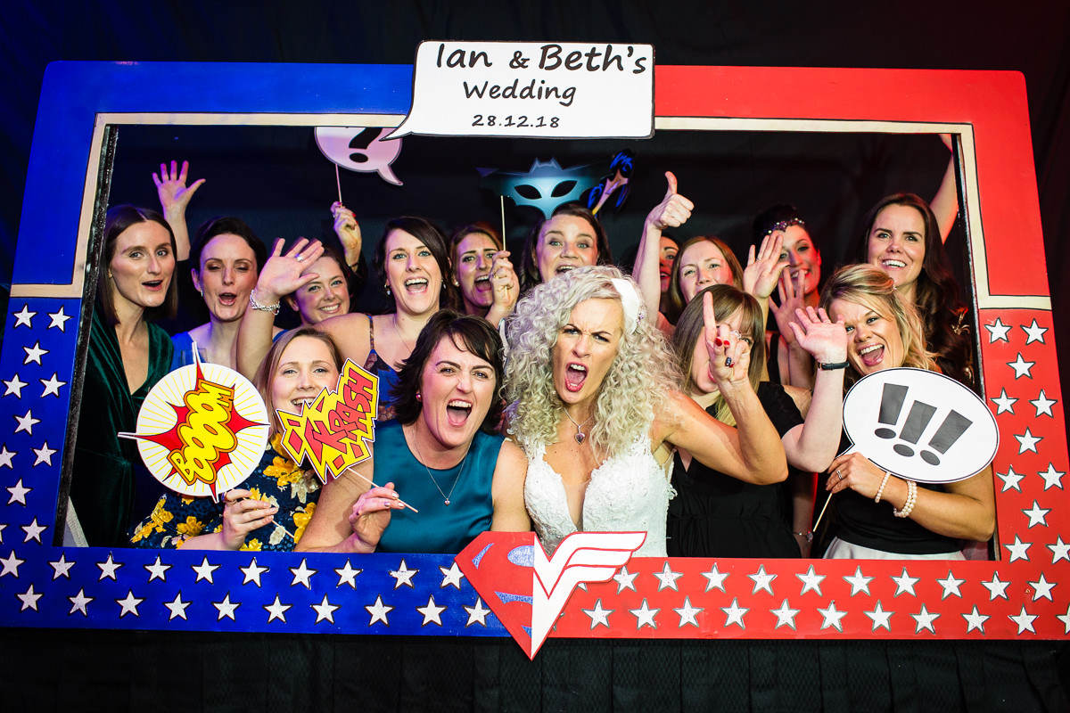 girls photo booth photo with expressive faces and super hero props - charlotte giddings photography