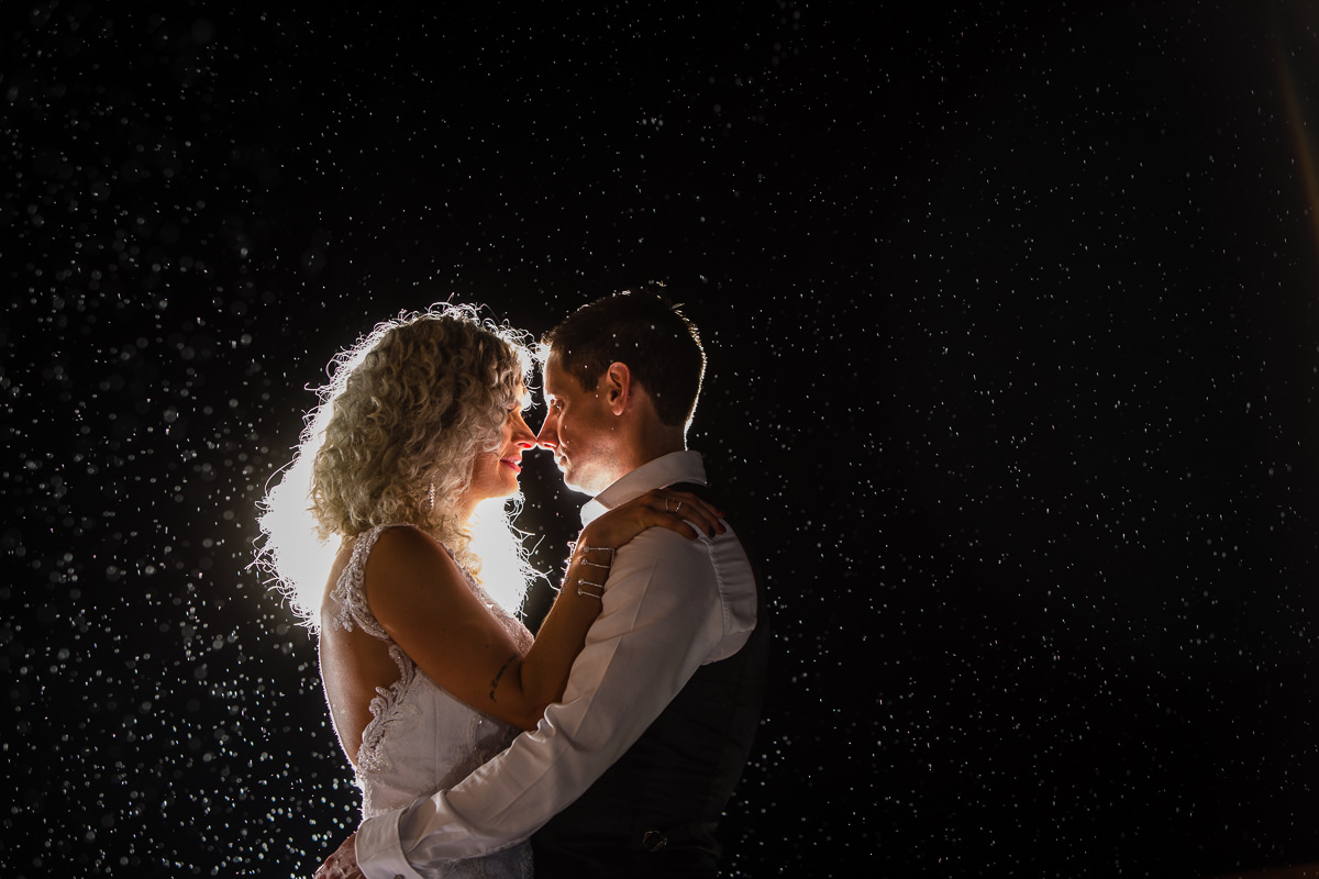 final shot of the night with bride and groom in the rain looking lovingly into ecah others eye at lake vyrnwy wedding