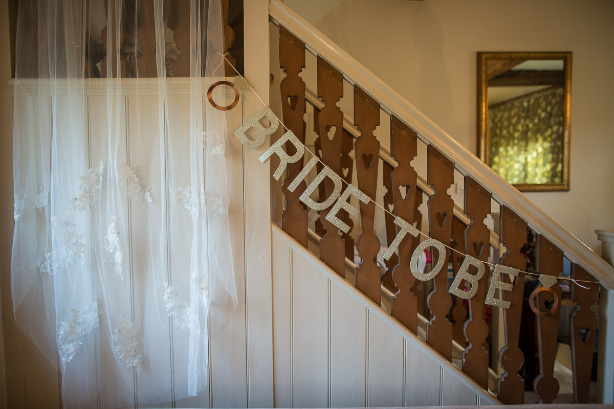 bride to be signage hanging on a staircase at combermere abbey