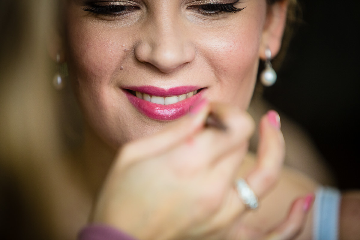 close up of a bride having lipstick applied to lips during bridal prep