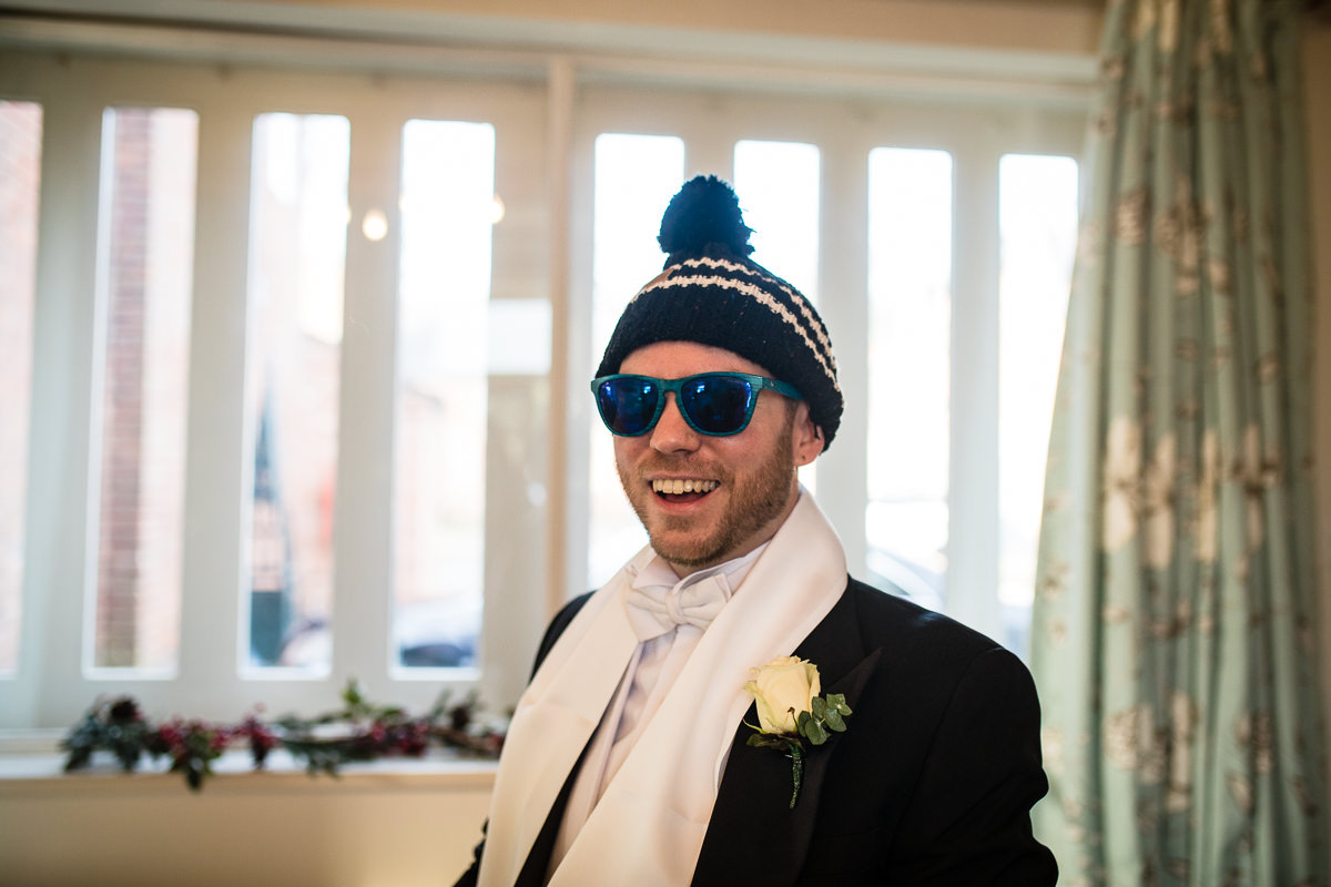 usher all suited up and wearing blue sunglasses and bobble hat, not part of wedding attire, charlotte giddings photography