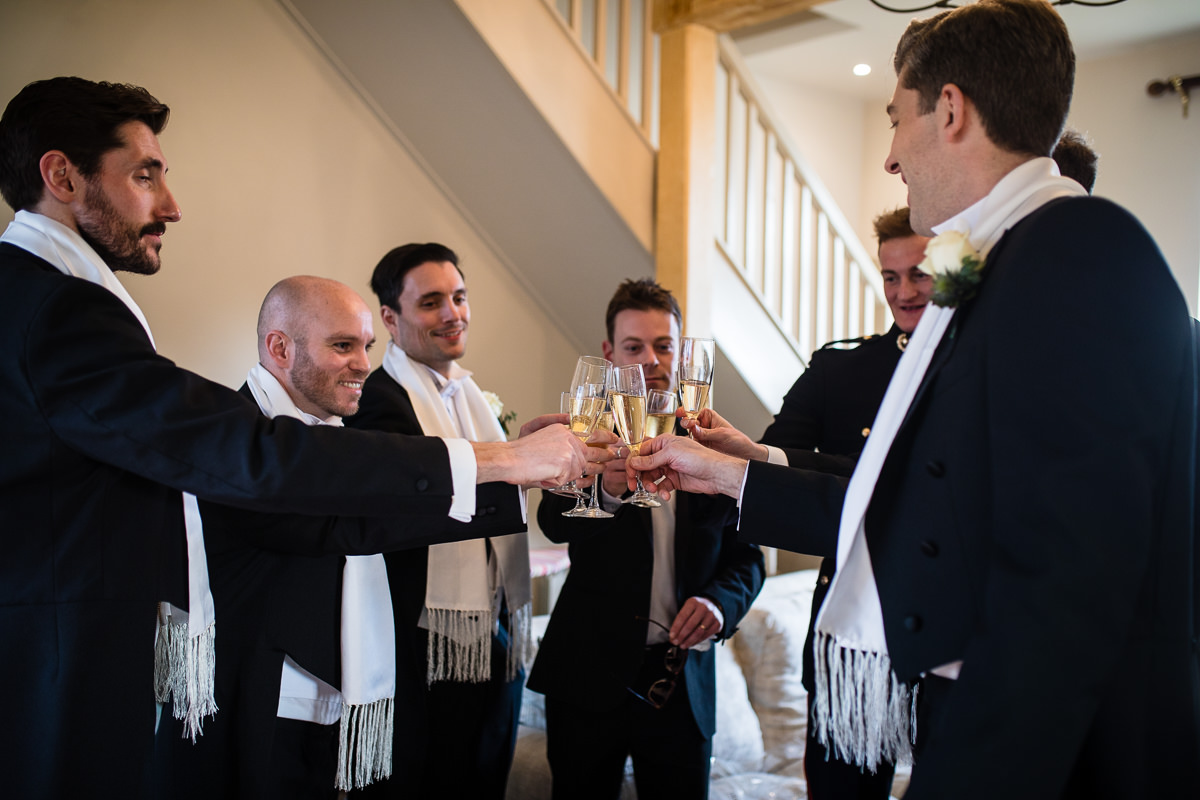 groom and groomsmen saying cheers! with champagne before they leave for the pub and church in audlem cheshire