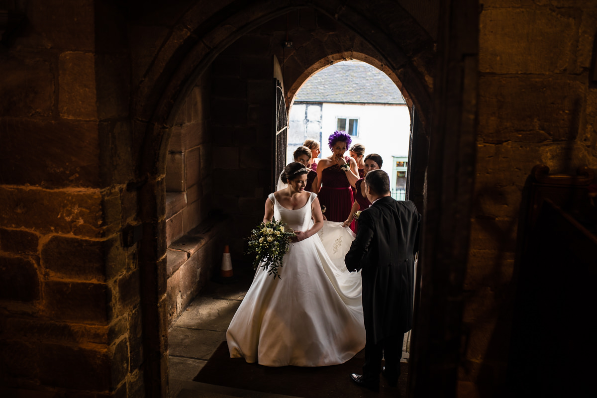 bride and bridesmaids getting dress organised in the doorway at st james the great church,audlem, cheshire