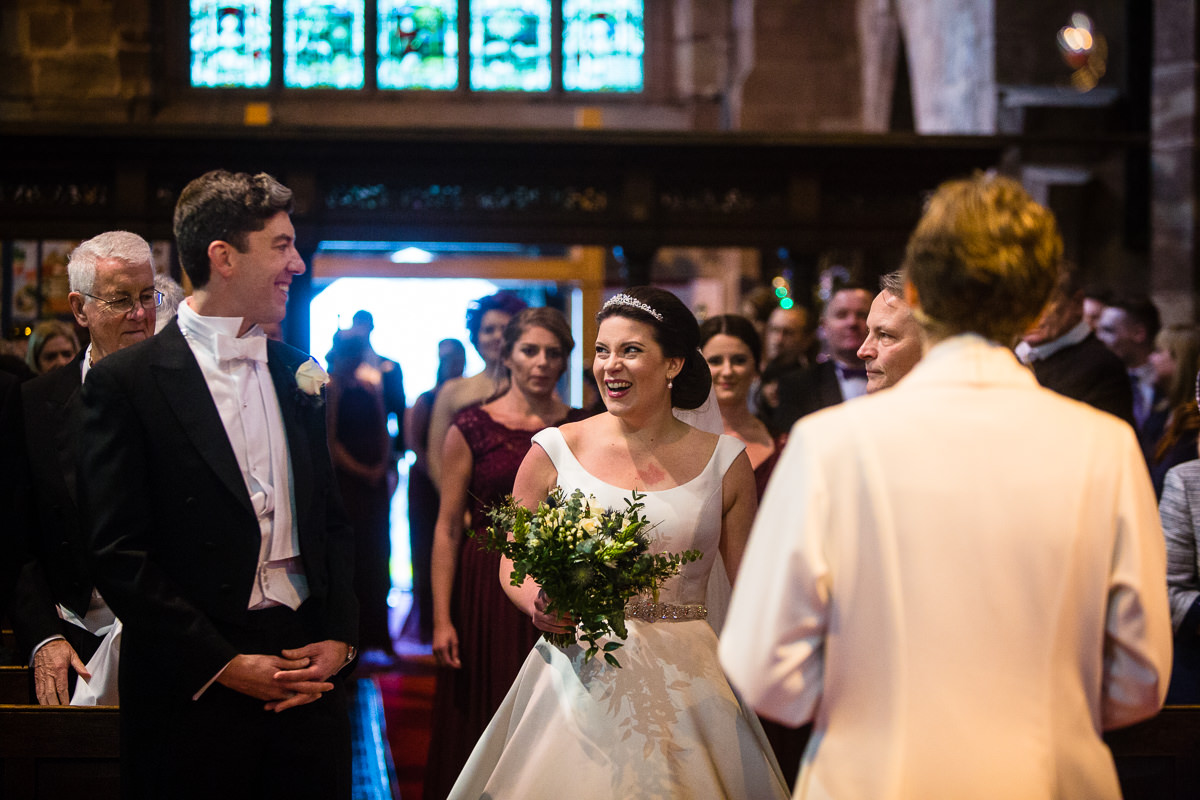 bride seeing her groom in church for first time, massive smile in st james the great church audlem, cheshire