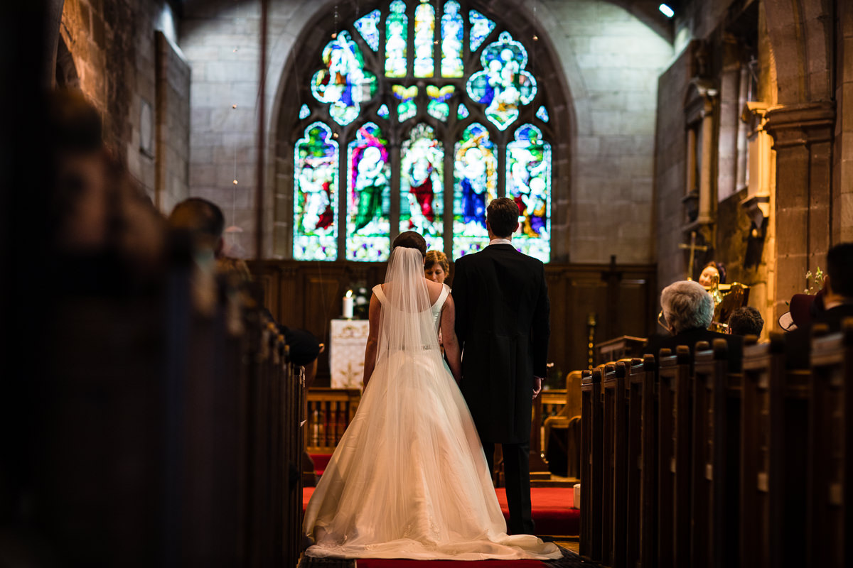 Bride and groom looking at the vicar in the stain glass window at the alter as she does a reading in st james the great church, audlem cheshire