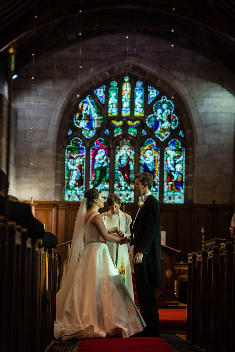 bride and groom looking at one another as they say their vows to each other in st james the great church, audlem, cheshire