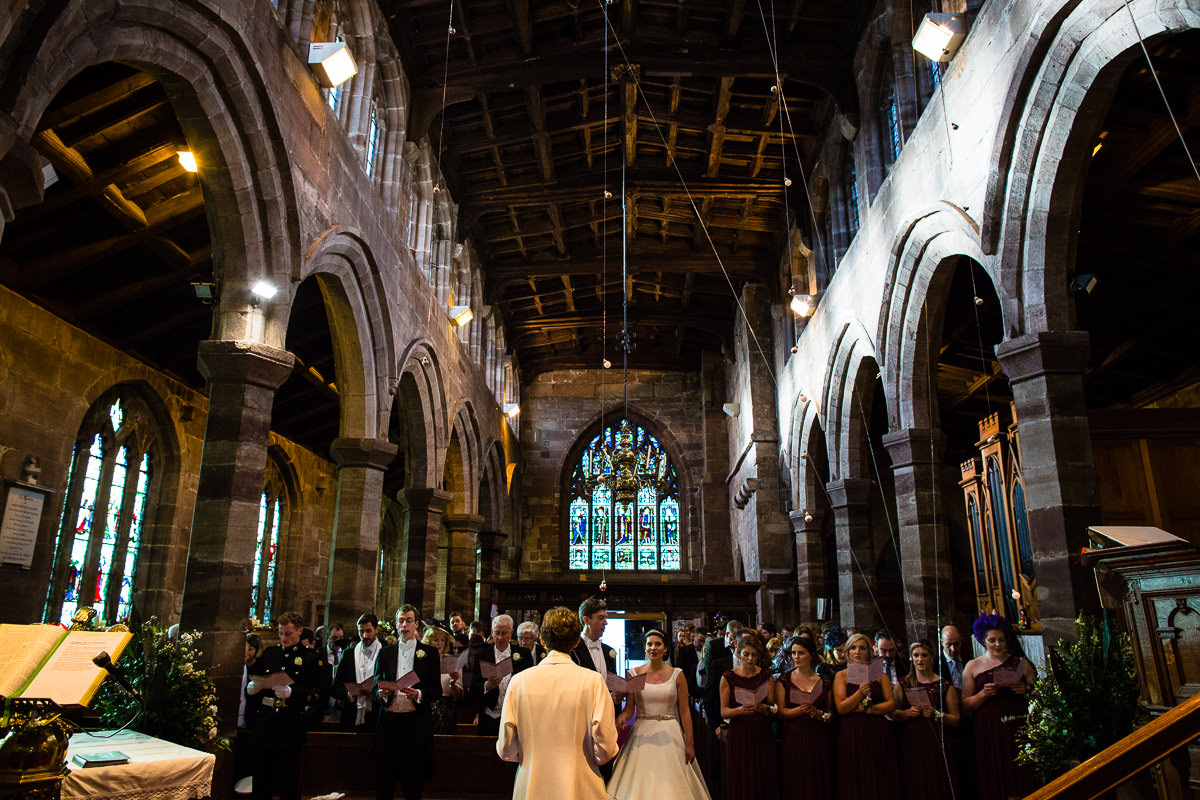 wide shot of st james the great church, audlem, cheshire whilst bride and groom amongst guests sing hymns, charlotte giddings photography