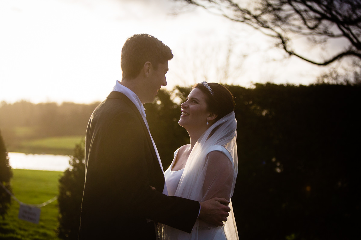 bride and groom looking at one another incredibly happy now they are married in beautiful golden hour outside combermere abbey wedding venue