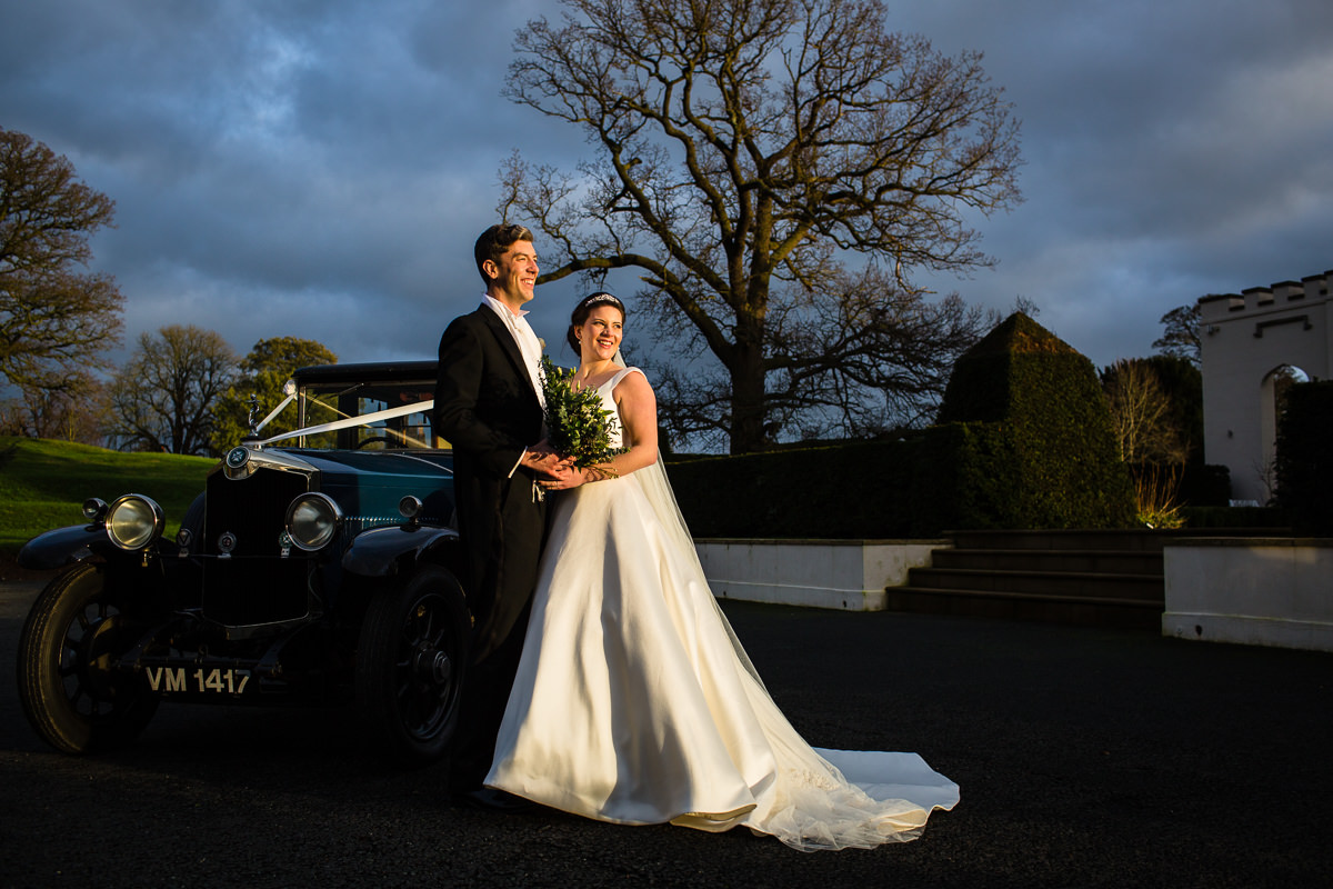 bride and groom outside combermere abbey in warm golden hour sunlight with the crosbey car