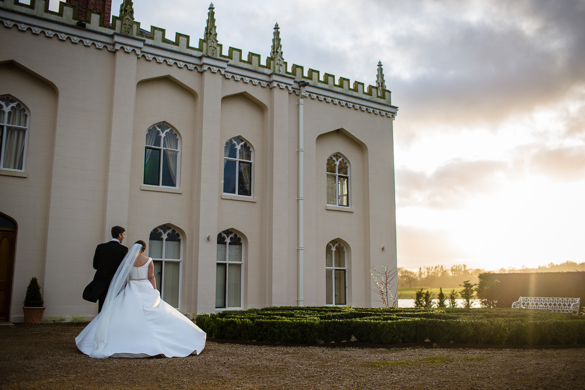 bride and groom walking around the side of combermere abbey in warm golden winter sunshine, charlotte giddings photography recommended photographer combermere abbey