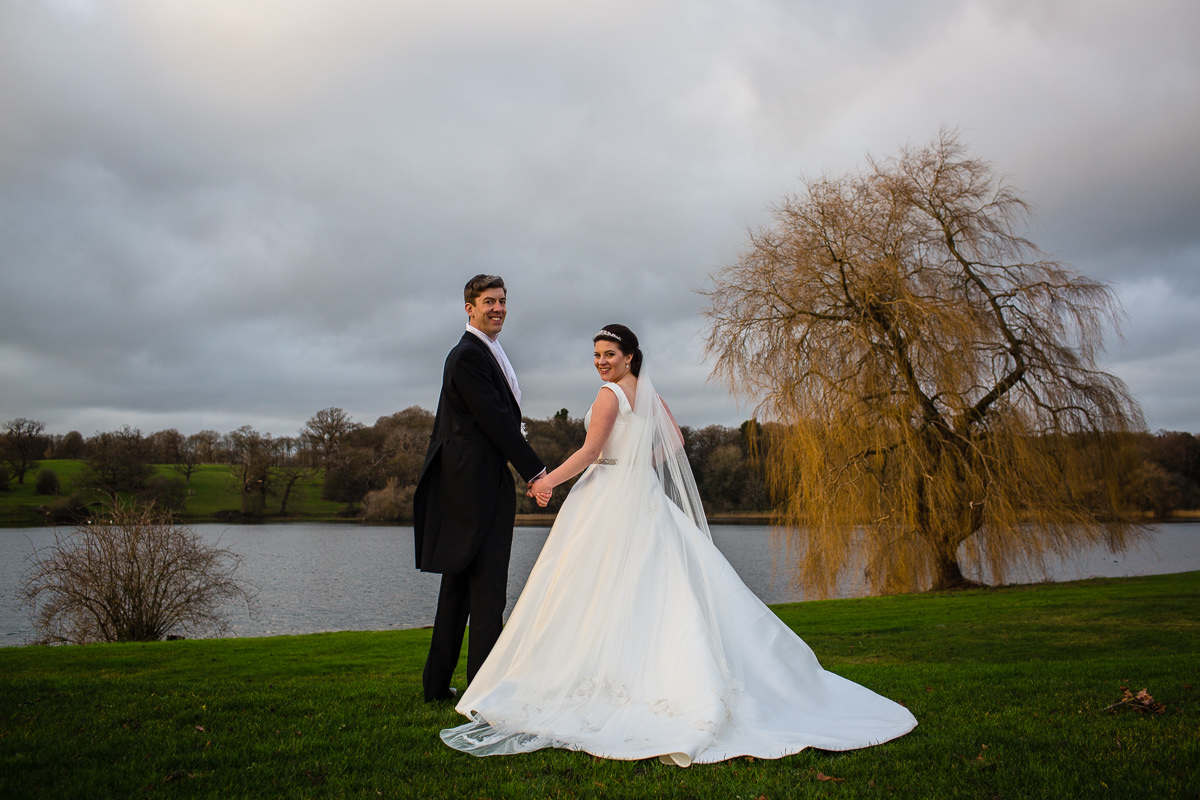 bride and groom holding hands as they look over their shoulders at the lake at combermere abbey in december, shropshire wedding photographer