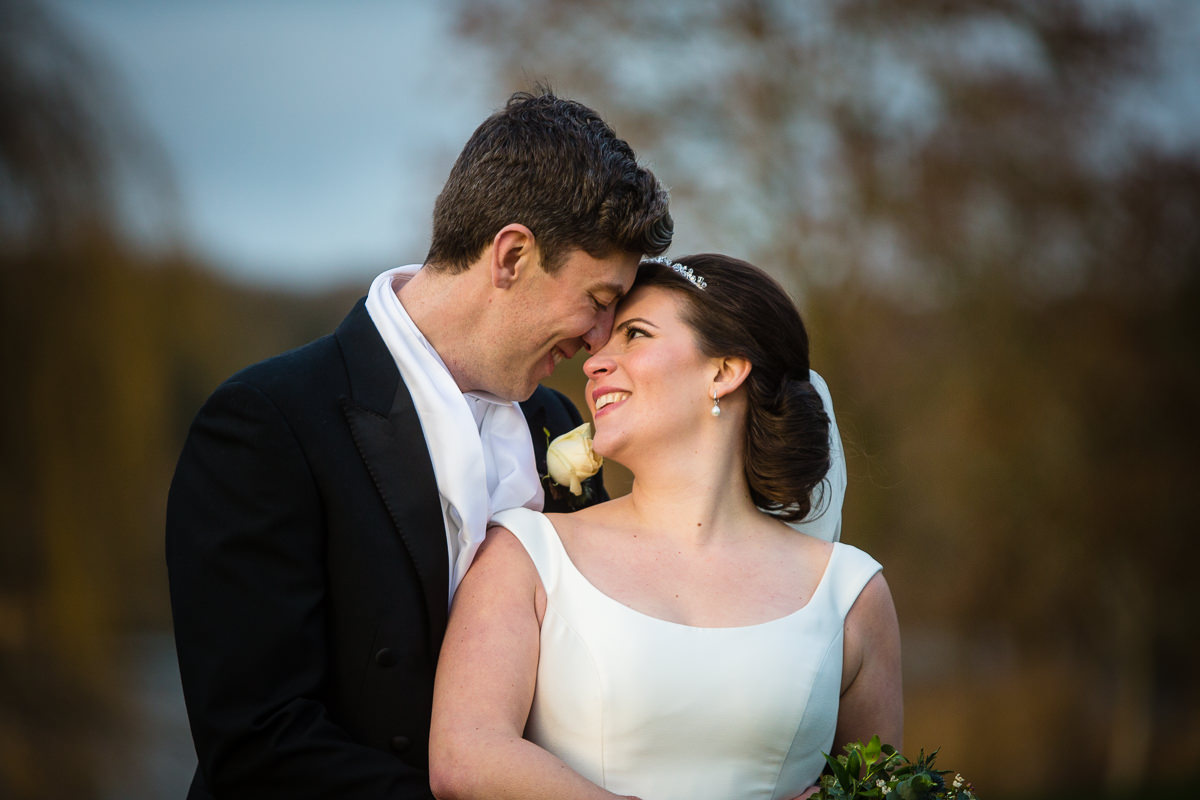 bride and groom heads close together looking lovingly into each others eyes at combermere abbey