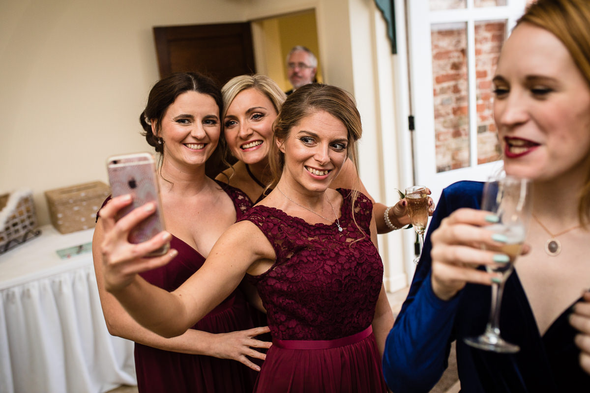 bridesmaids taking a selfie together looking really happy at friends wedding at combermere abbey